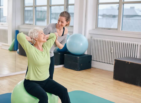 Mature woman working out on a fitness ball with help from personal trainer at gym.