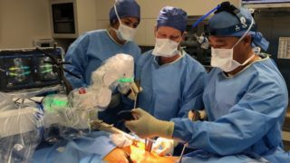 Dr. Johnson performing robotic spine surgery.
