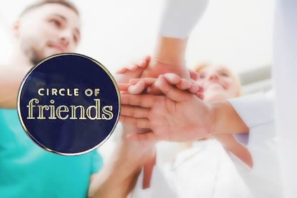 Medical service teamwork - Doctor, surgeon and nurse join hands together with Circle of Friends pin over top.